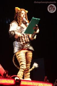 Yuriko a színpadon, épp konferál